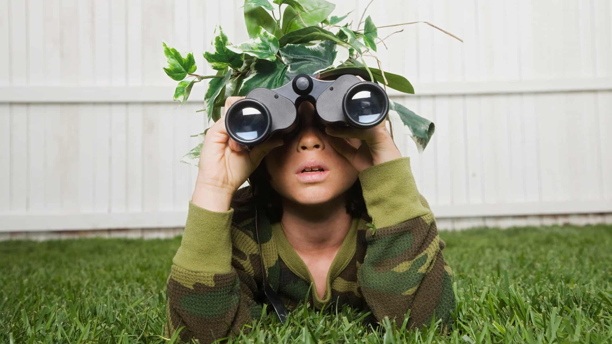 a child dressed in army fatigues lies on the ground in his backyard wearing leaves and branches on his head as camouflage and peering through a pair of binoculars in a soldier pose.