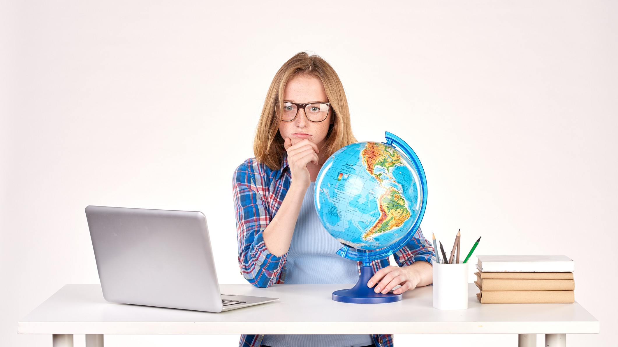 a woman sits at her desk looking puzzled and disappointed with her hand to her chin while an open laptop computer sits on one side of her and her hand is around the base of a globe of the world on the other side of her.
