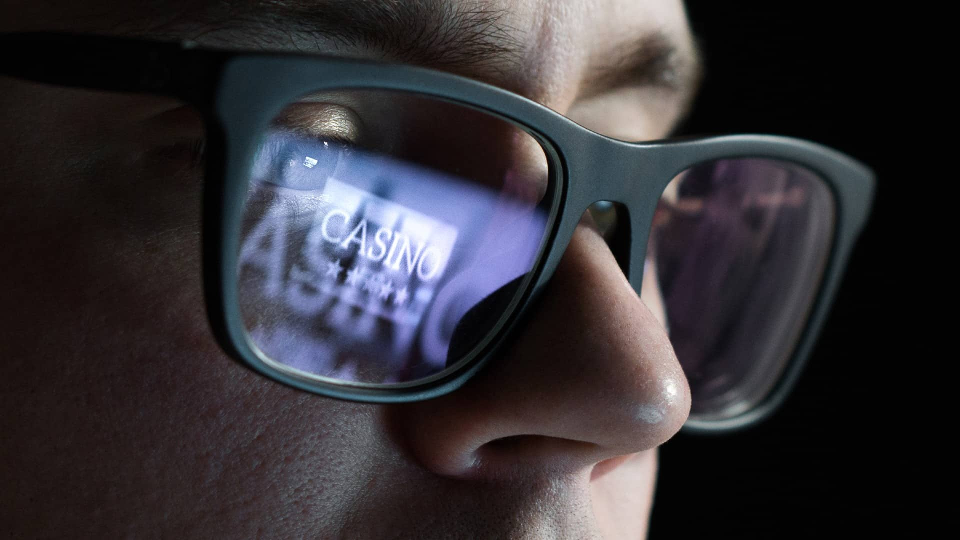 """a close up of a man wearing dark glasses with the word """"casino"""" and stars reflected in the glass of one of his eyes."""