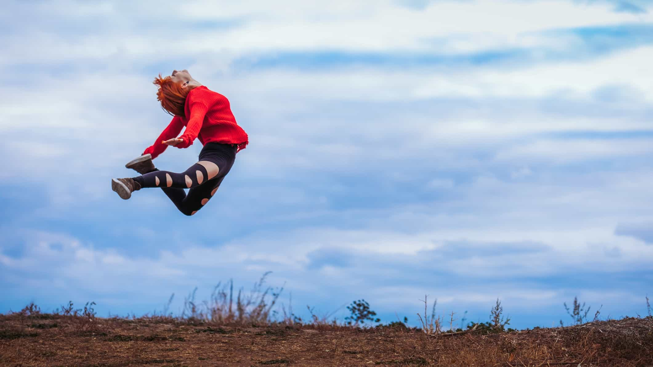 A woman wearing a red jumper leaps into the air with sky behind her and earth beneath her.