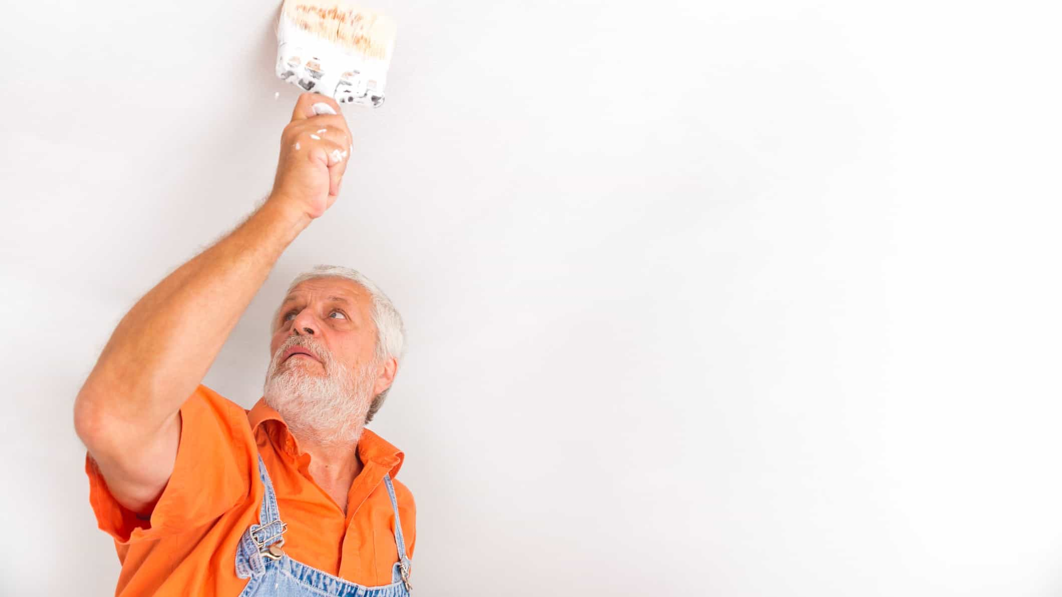 An older man in an orange shirt paints the ceiling of a house.