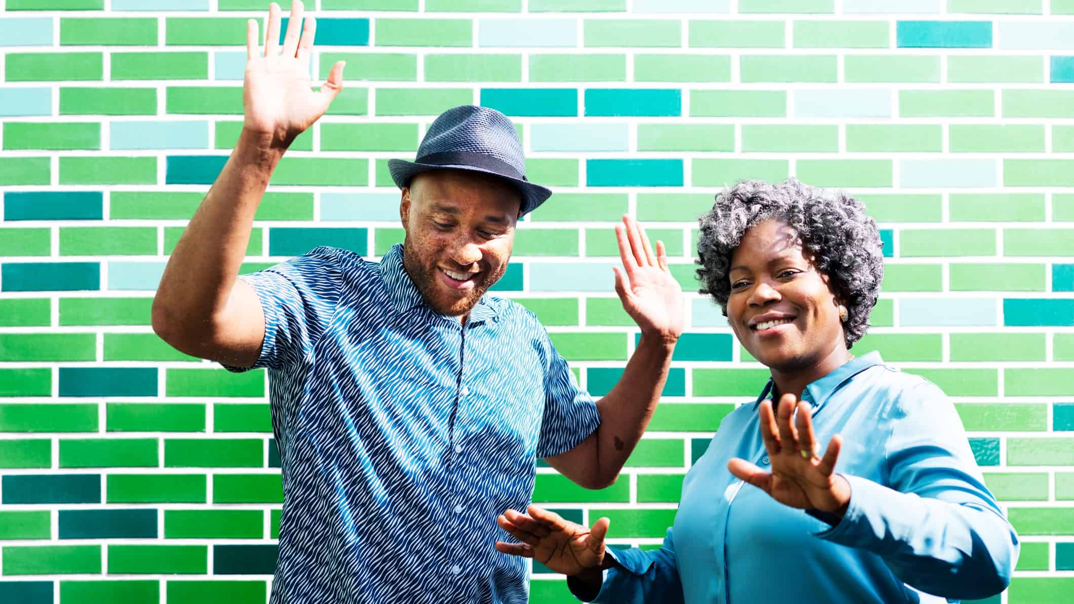 A man and woman put hands in the air as they dance in front of a green brick wall.