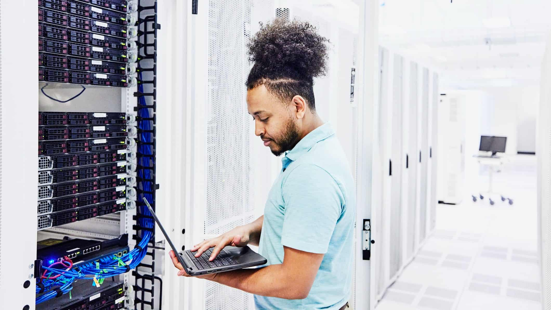 Cybersecurity company employee looks at laptop while standing near server room
