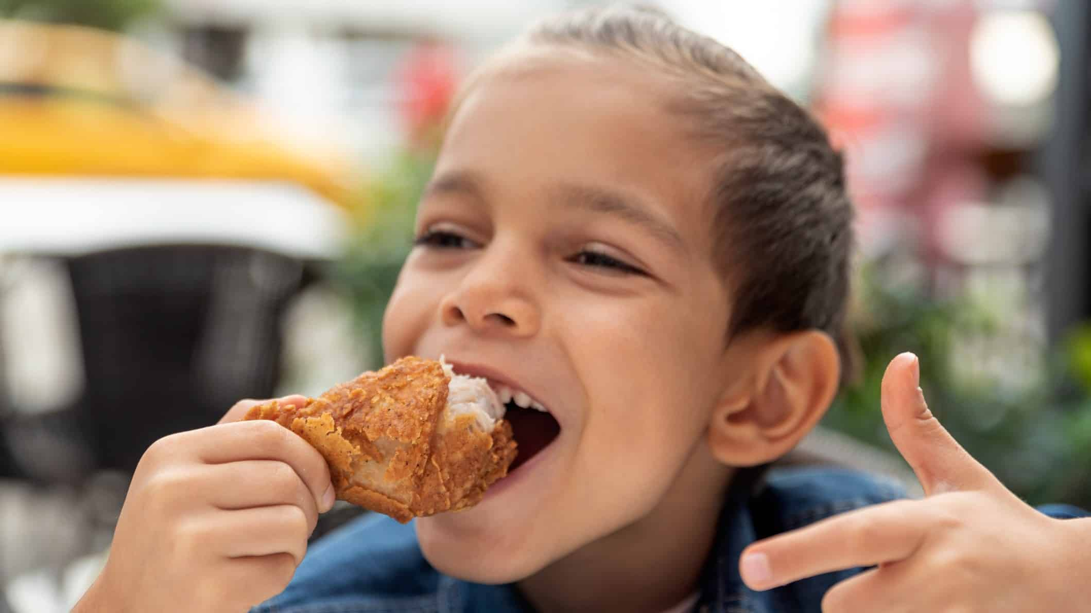 A young boy points and smiles as he eats fried chicken.