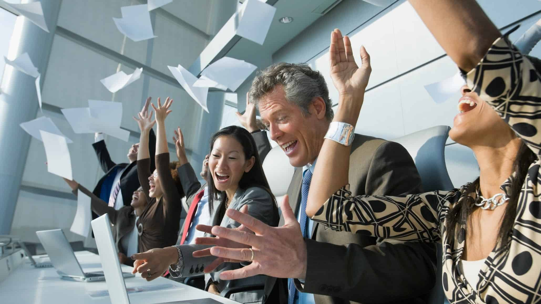 A group of happy office workers throw papers in the air and cheer.