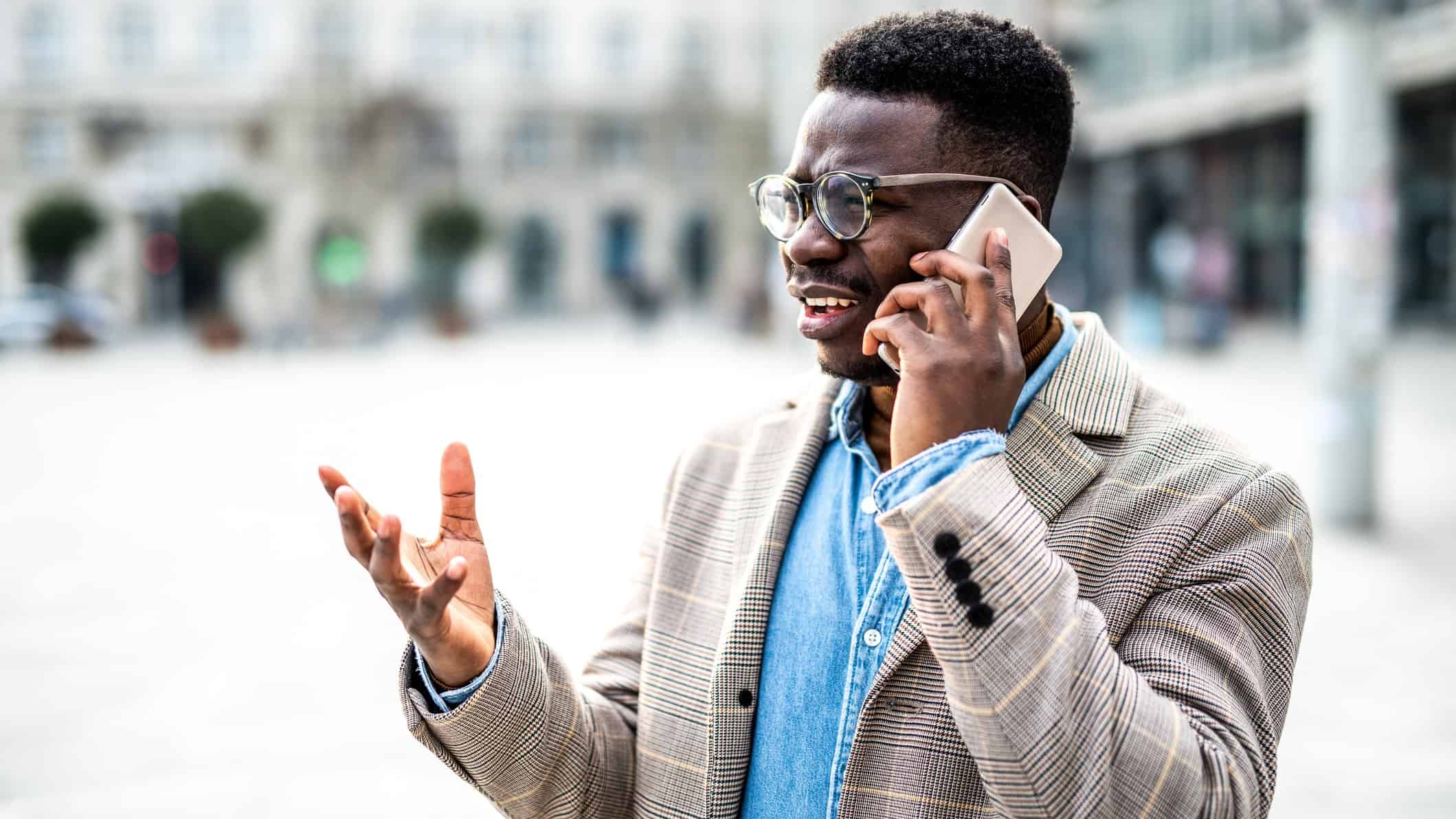 A man talking on his mobile phone looks uncertain