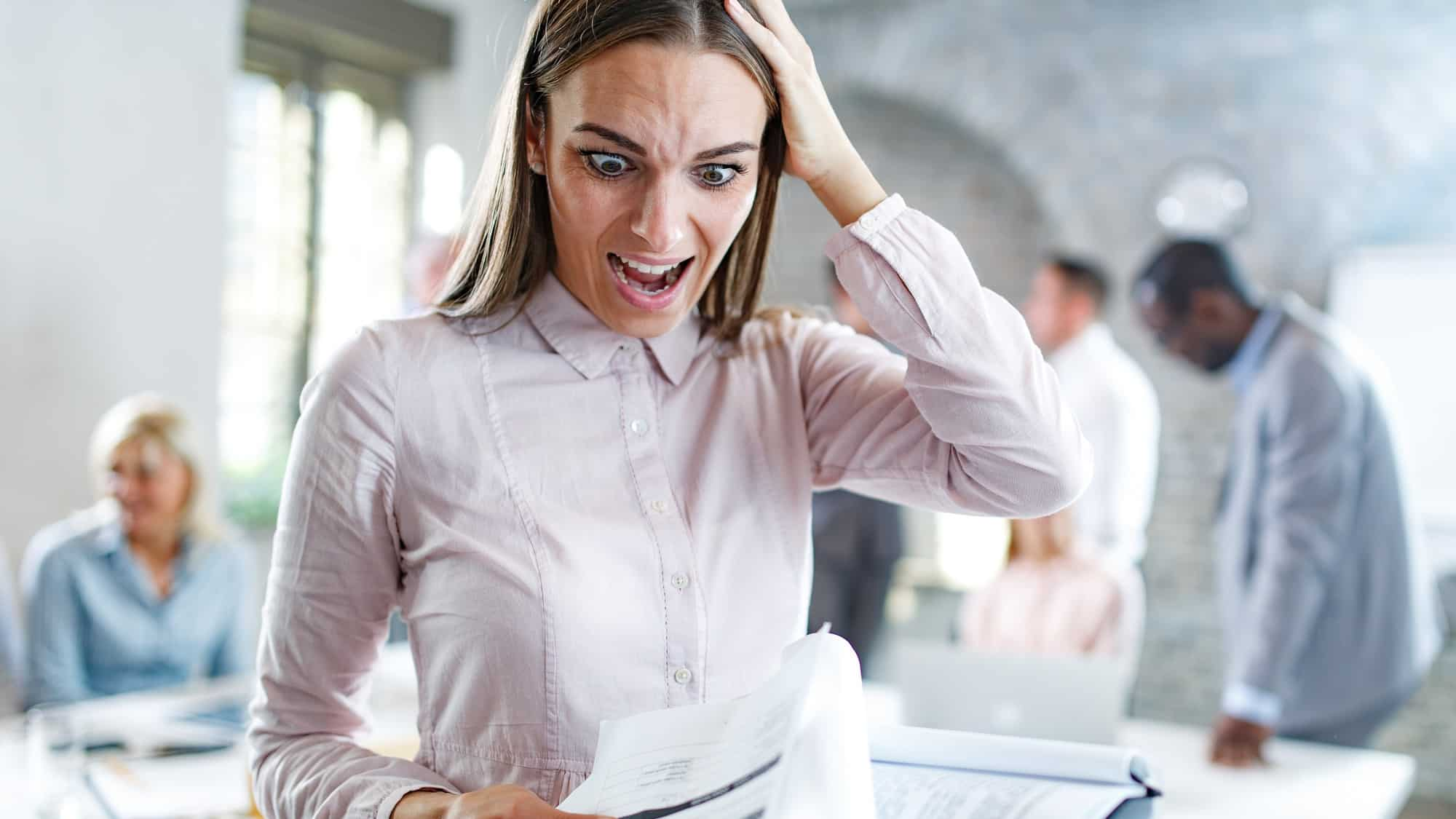 Young businesswoman analyzing shocking paperwork in disbelief at the office. Her colleagues are in the background.