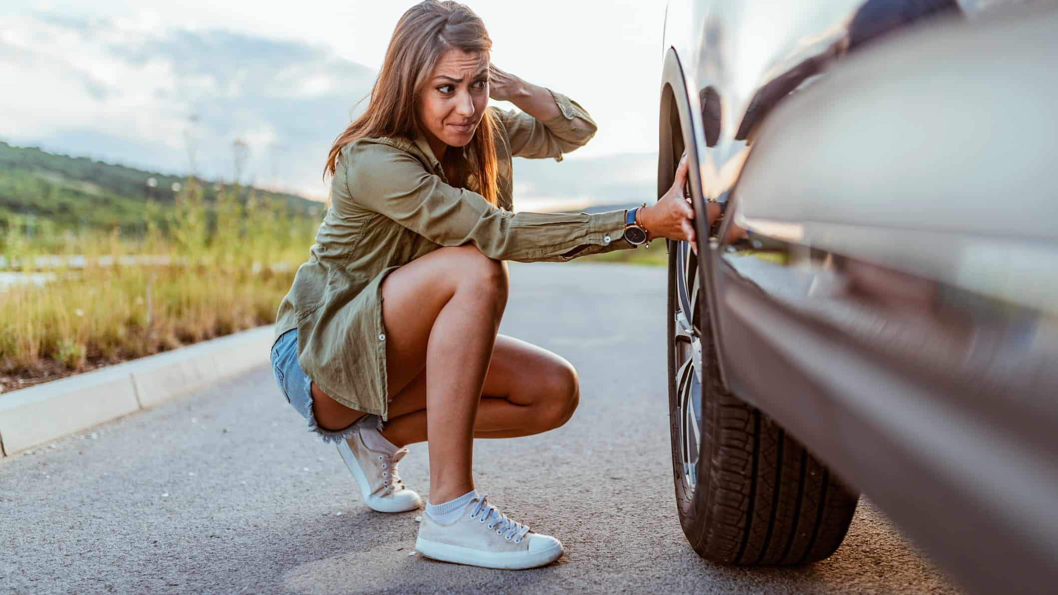 A woman stops on a road to check the tyre or wheel on her car